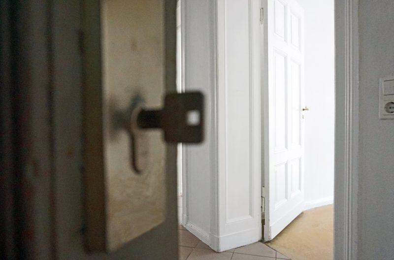Durch eine offene Tür blickt man in eine leere Wohnung. Der Schlüssel zur Tür steckt im Schloss.