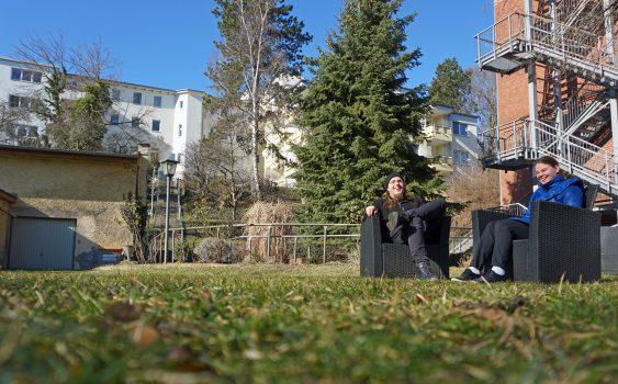 Zwei Personen sitzen auf dem Gelände der Rothenburgstraße in Gartensesseln und lachen. In Hintergrund sieht man ein Teil der Gebäude des Blindenhilfswerkes Berlin e.V.