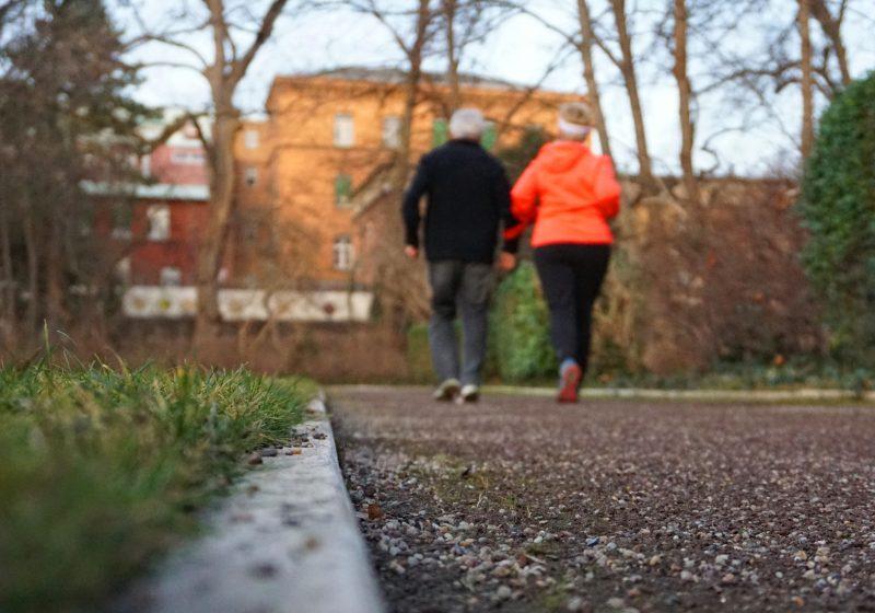 Zwei Personen joggen auf einer Laufstrecke. Eine der beiden trägt ein leuchtendes Oberteil und hält sich an einem roten Band, das sich am Arm der anderen Person befindet, fest.