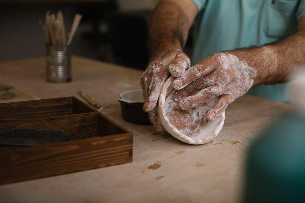 Eine Person formt an einem Tisch ein kleines Gefäß aus Ton. Man sieht nur seine Hände. Auf dem Tisch befinden sich außerdem ein Holzkästchen mit Fächern und ein Glas voller Pinsel.
