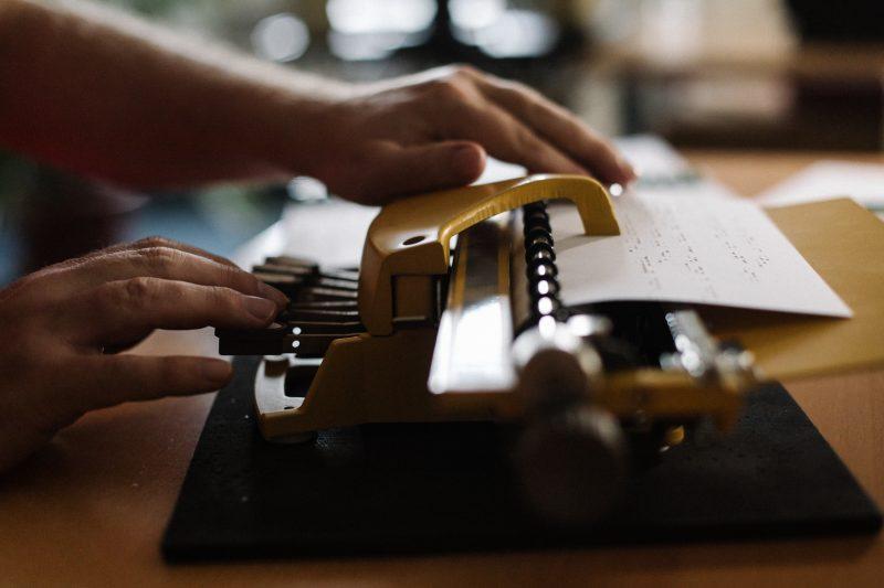 An einer Braille-Schreibmaschine wird gerade ein Dokument aufgesetzt. Man sieht lediglich das Gerät mit einem Stück Papier und die Hände des Nutzers.