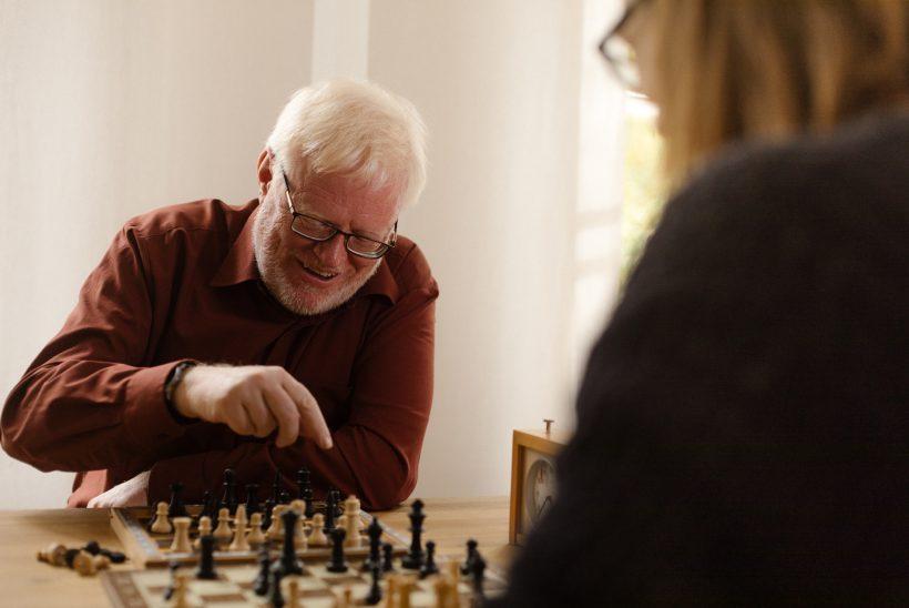 Ein älterer Mann mit weißen Haaren und Brille sitzt einer anderen Person, die nur unscharf zu erkennen ist, gegenüber. Sie spielen Schach. Der Herr ist am Zug und lächelt.
