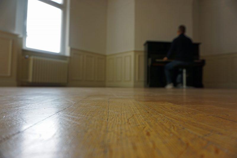 Eine Person sitzt an einem Klavier, dass sich an der hinteren Wand des ansonsten leeren Raumes mit Parkettboden befindet.