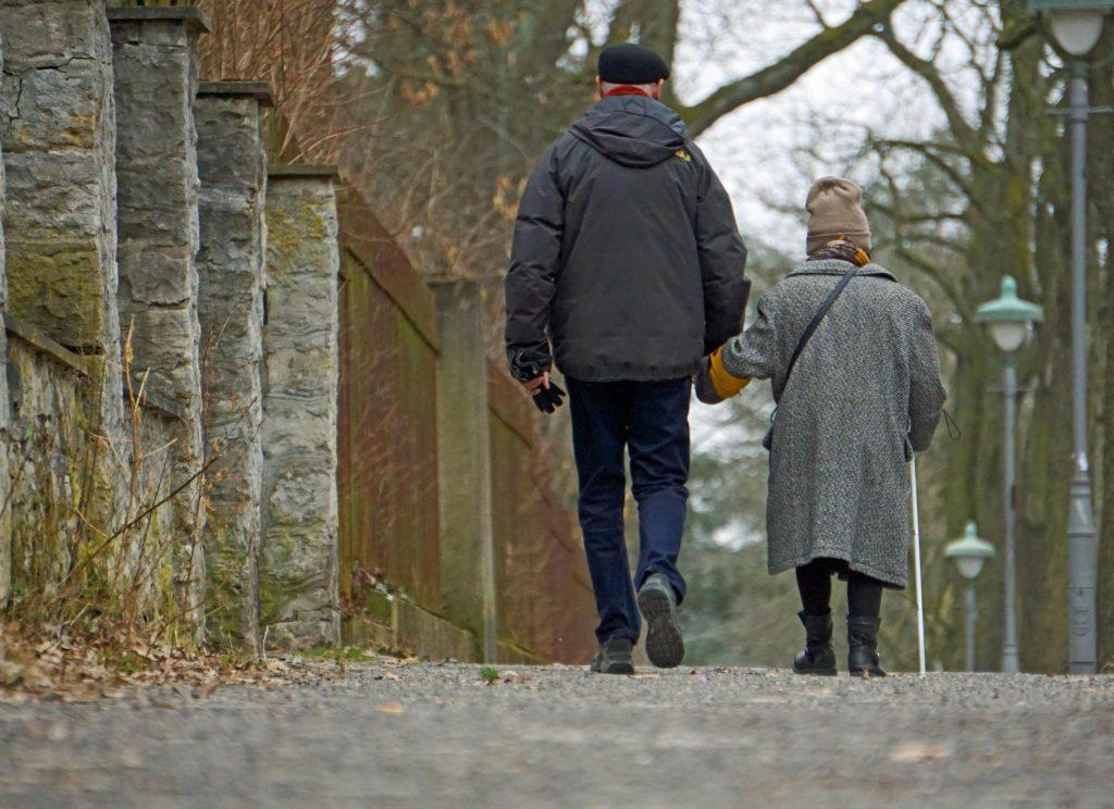 Zwei Personen gehen Hand in Hand in einem ruhigen Stadtbezirk spazieren. Sie kehren der betrachtenden Person den Rücken zu. Rechts befindet sich eine ältere, kleine Dame mit Mütze und Mantel. Sie nutzt zusätzlich einen Langstock und trägt eine Armbinde mit Blindenabzeichen. Der Herr, links auf dem Bild, mit schwarzer Schiebermütze, ist circa 50 cm größer.