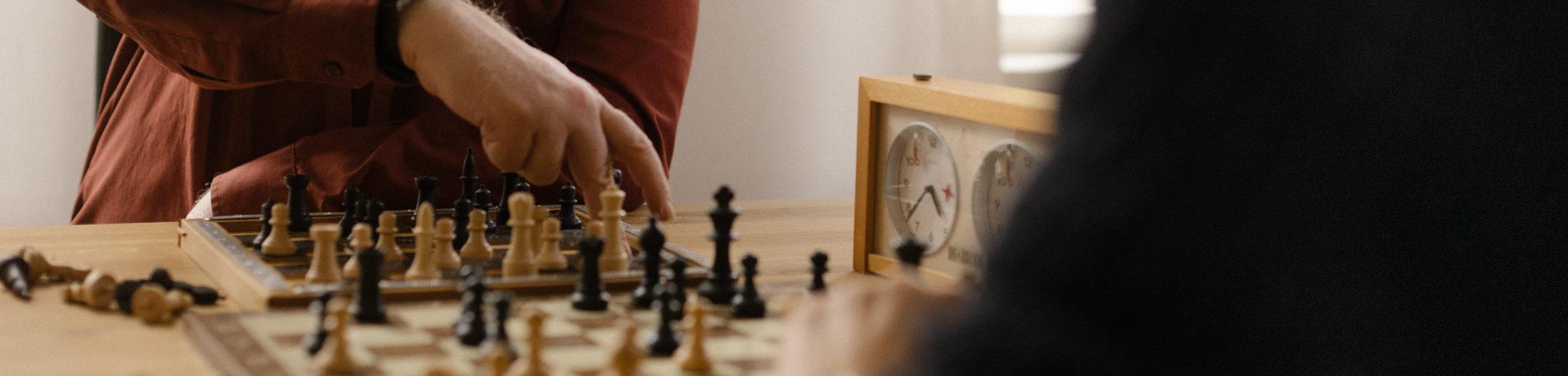 Zwei Personen spielen Schach. Von den Personen sieht man lediglich kleine Ausschnitte. Vor allem das Schachspiel nimmt einen Großteil des Bildes ein.
