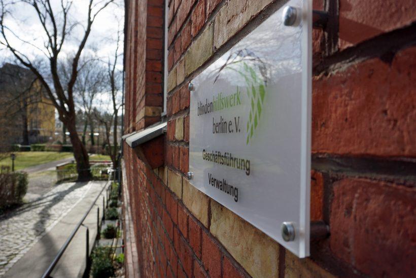 An einer Häuserwand aus Backsteinen ist ein weißes Schild angebracht. Darauf st das Logo vom Blindenhilfswerk Berlin e.V. zu sehen. Außerdem steht darauf