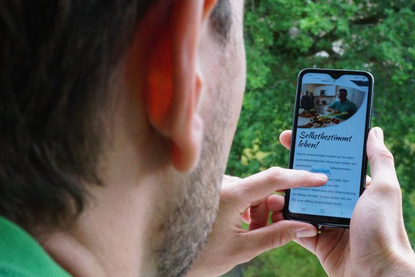 Ein Mann schaut sich die neue Website des Blindenhilfswerks Berlin e.V. an.