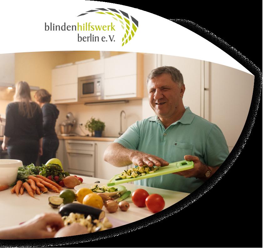 Ein Mann sitzt an einem Tisch voller Gemüse. Der Herr schiebt bereits kleingeschnittene Zucchini von einem Brett auf einen Teller und lacht. Ihm gegenüber sitzt eine weitere Person, man sieht allerdings nur die Hände. Im Hintergrund befinden sich zwei weibliche Personen. Sie stehen am Herd und kochen.