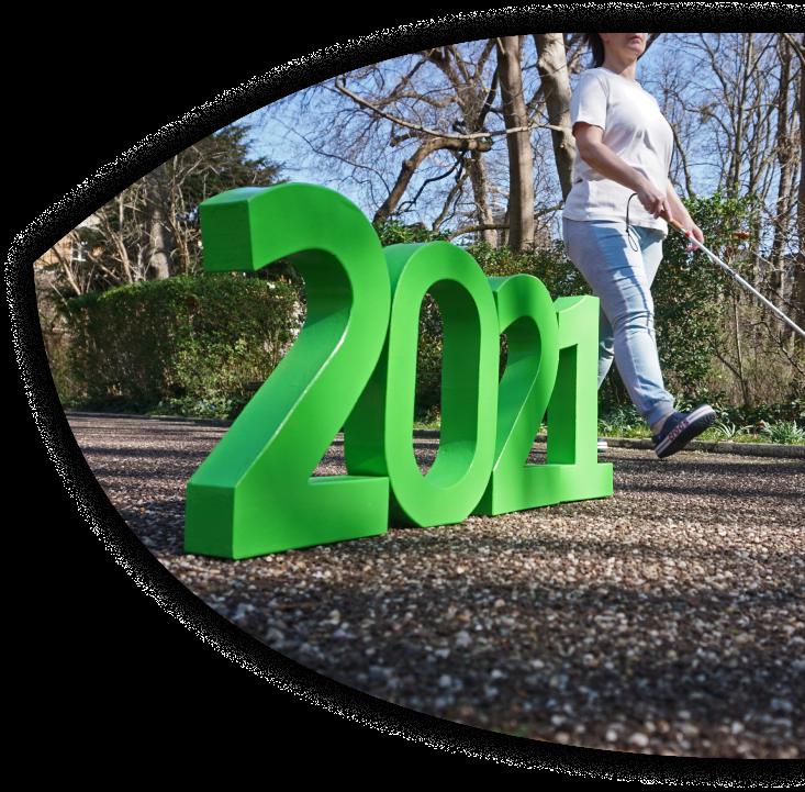 Vier große, grüne Zahlenfiguren stehen auf einem festen Weg und bilden die Zahl 2021. Daran vorbei läuft eine Frau mit einem Langstock.