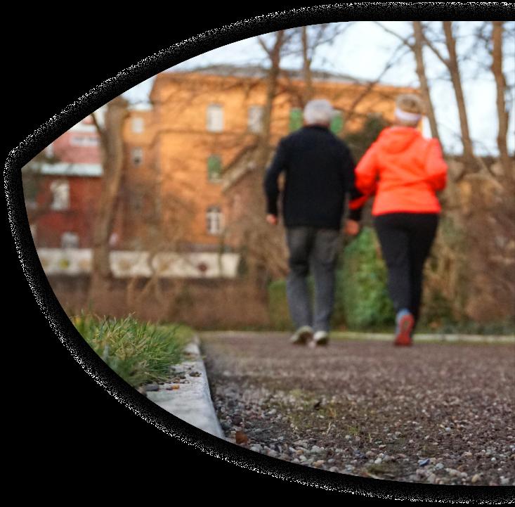 Ein Mann mittleren Alters und eine jüngere, sehbehinderte Frau fahren auf einem Tandem einen gepflasterten Radweg entlang. Der Herr sitzt vorne und lenkt, die Dame hinten. Beide lächeln. Im Hintergrund sieht man ältere Backsteingebäude.