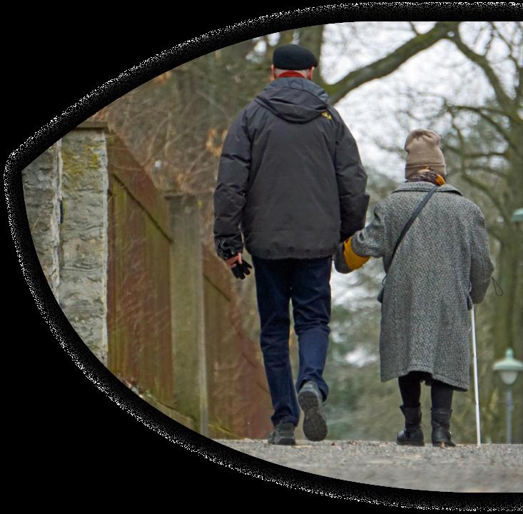 Zwei Personen gehen Hand in Hand in einem ruhigen Stadtbezirk spazieren. Rechts befindet sich eine ältere, kleine Dame mit Mütze und Mantel. Sie nutzt zusätzlich einen Langstock und trägt eine Armbinde mit Blindenabzeichen. Der Herr, links auf dem Bild, mit schwarzer Schiebermütze ist circa 50 cm größer. Beide sind nur von hinten zu sehen.