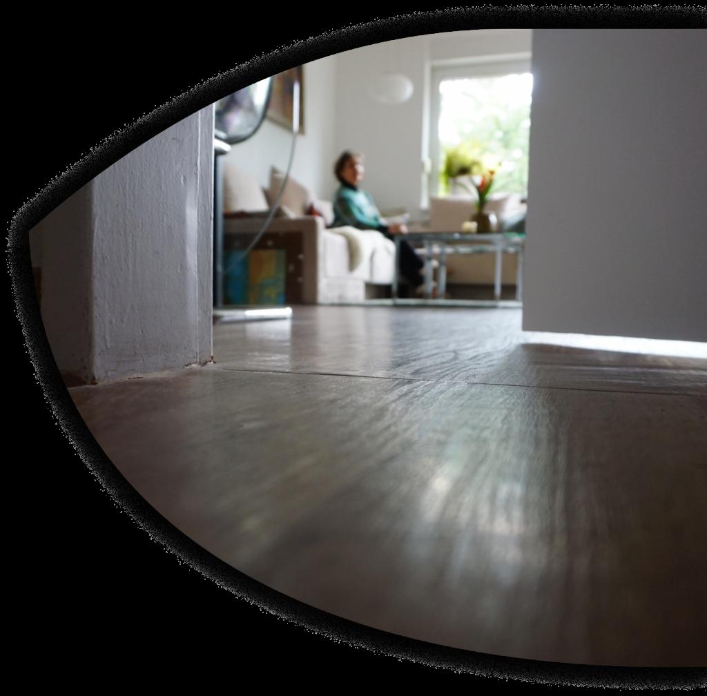 Vom Boden aus blickt man durch eine halbgeöffnete Tür in in einen Raum, in dem eine Person auf einem Wohnzimmersofa sitzt.