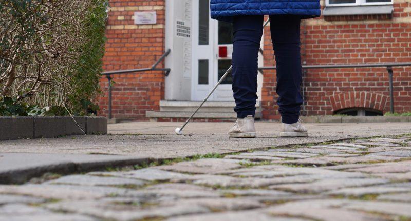 Eine Person mit Langstock steht vor einem Backsteingebäude. Dem Betrachter ist der Rücken zugewandt.