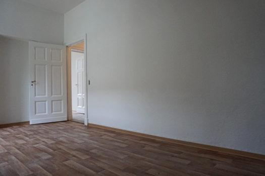 Eine leere Wohnung mit weißen Wänden. Die Tür zum Flur steht offen.