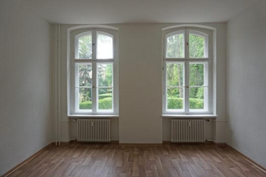 Eine leere Wohnung. Durch zwei große Fenster kann man Teile eines Parks erkennen.