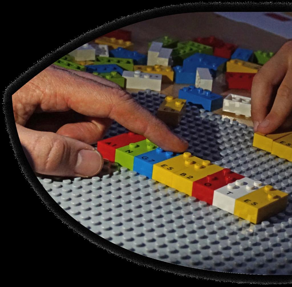 Zwei Hände fahren über Legosteine, die sich auf einer Platte befinden. Es handelt sich um Braille Bricks, Legosteine zum spielerischem Erlernen der Brailleschrift.