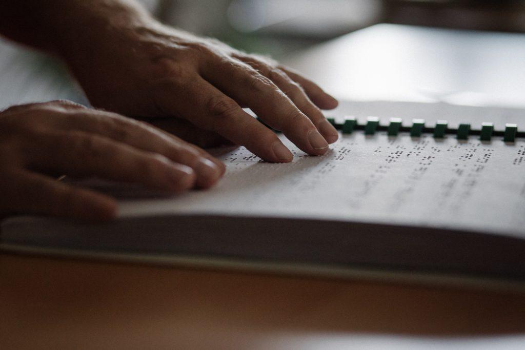 Eine Person liest ein Buch in Brailleschrift. Von der Person sind lediglich beide Hände zu sehen.