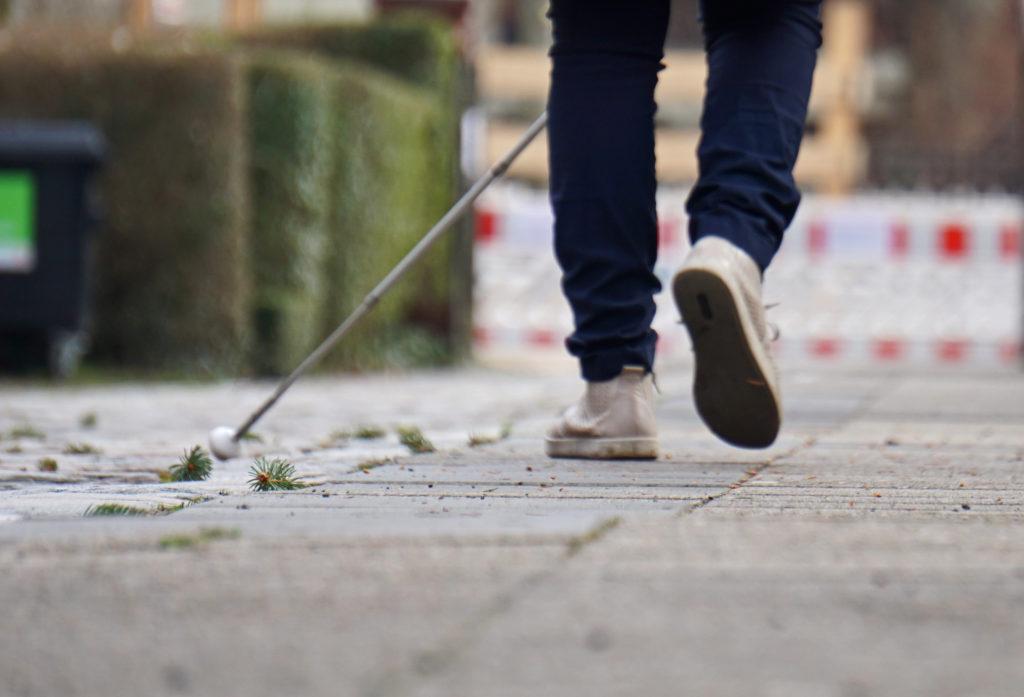 Eine Person läuft mit Langstock einen Weg entlang. Man sieht lediglich die Beine.