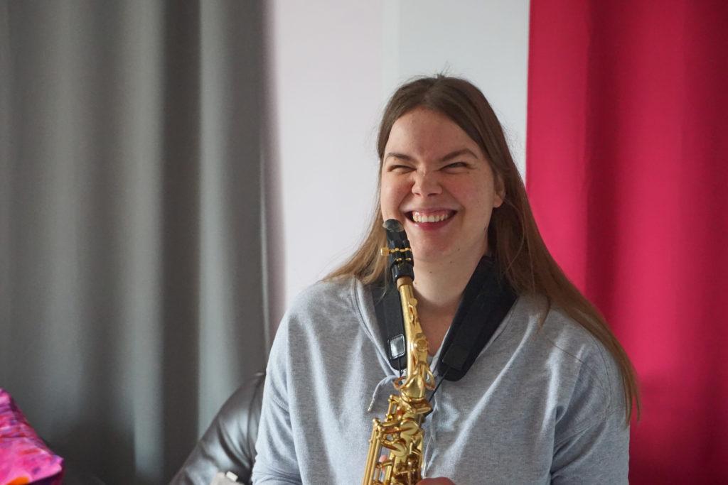 Eine junge Frau spielt Saxophon. Sie lacht.