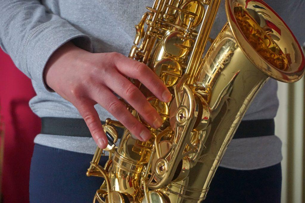 Eine Person spielt Saxophon. Lediglich ein Teil des Saxophons und der Person ist zu sehen.