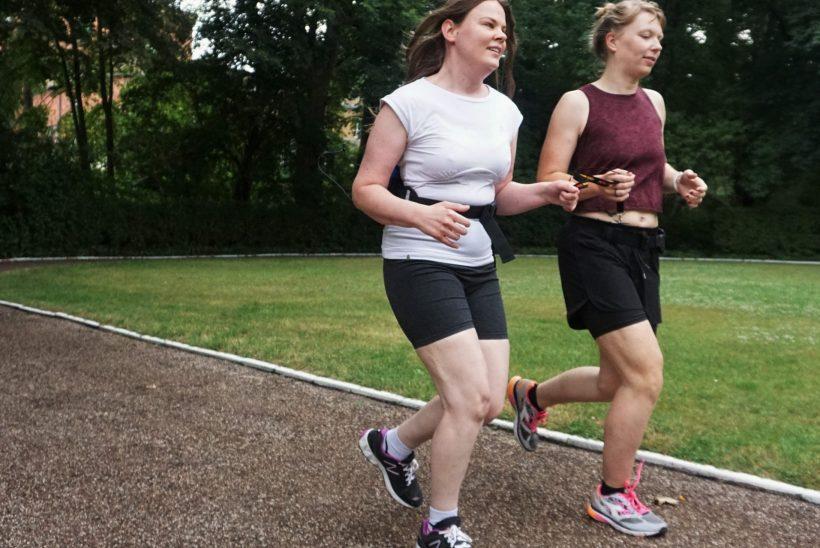 Zwei Frauen joggen nebeneinander auf einer Laufstrecke. Beide halten gemeinsam ein Band fest.