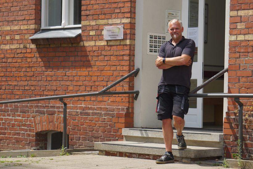 Lukas Ittner steht vor dem Gebäude der Rothenburgstraße 15. Er lächelt.
