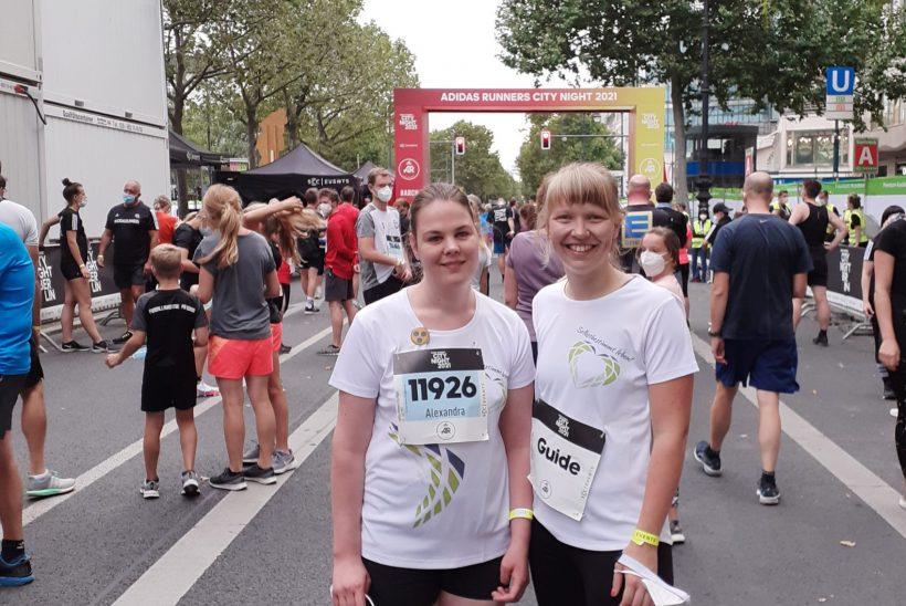 Zwei Frauen stehen im Startbereich eines Straßenlaufs. Die linke Dame ist Läuferin und die rechte ihr Guide.