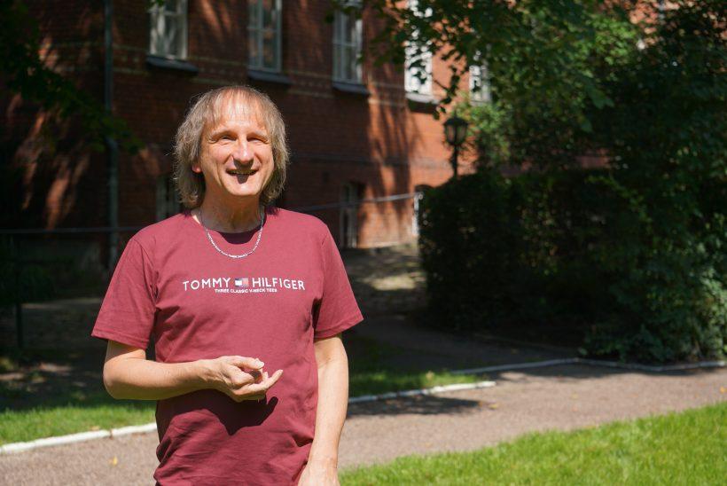 Ein Mann im mittleren Alter steht vor einem Backsteingebäude.