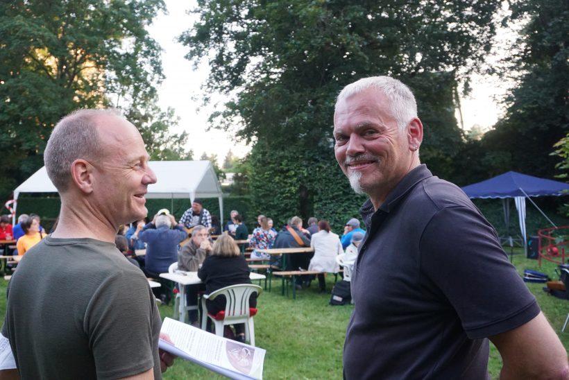 Herr Zehe (links) und Herr Ittner (rechts) stehen draußen und lächeln. im Hintergrund befinden sich Menschen, die an Bierbänken sitzen.