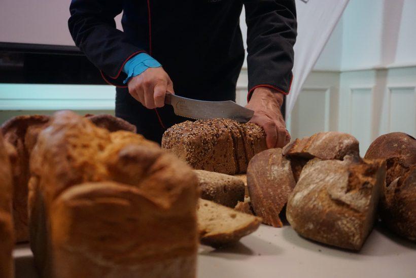 Eine Person schneidet Brot. Nur der Oberkörper ist zu sehen. Drum herum liegt Brot.