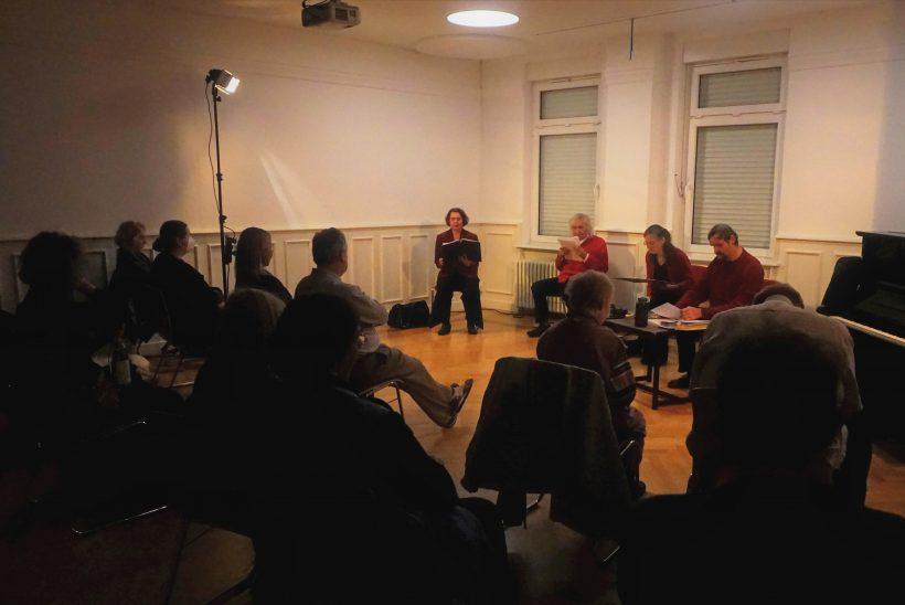 Vier Leute sitzen in einem vorderen Bereich eines Saales. Vor ihnen sitzt das Publikum.