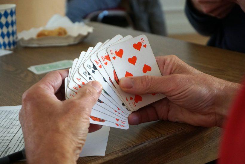 Zwei Hände halten Skatkarten mit Brailleschrift.
