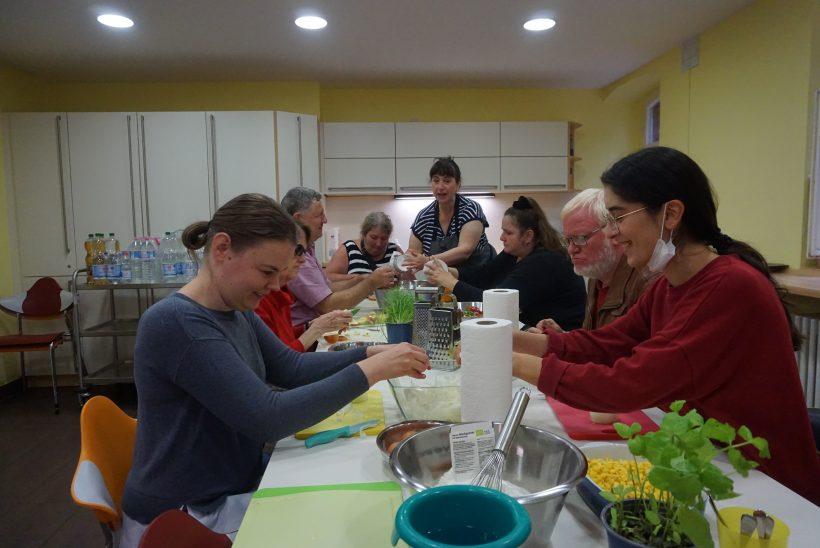 Mehrere Personen sitzen an einem Tisch in einer Küche. Auf ihm stehen Bananen, mehrere Schüsseln, Kräutertöpfe. Die Personen bereiten Essen zu.
