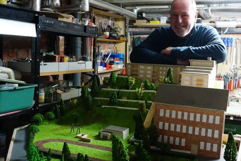 Ein Mann steht in einer Kellerwerkstatt hinter einem Geländemodell.