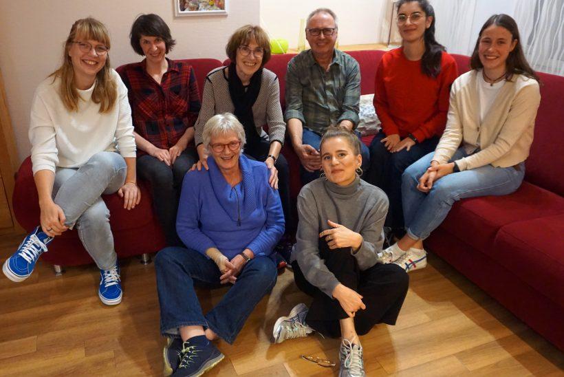 ISechs Personen sitzen auf einer roten Couch. Zwei Personen sitzen davor auf dem Boden. Es sind sieben Frauen verschiedensten Alter und ein Mann im Rentenaltern.
